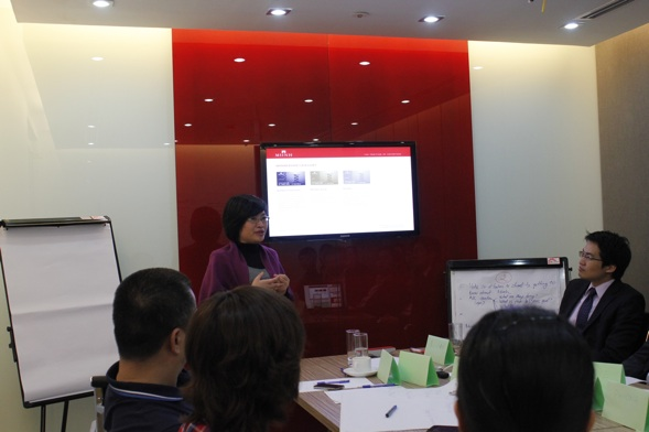Vu Hanh Nga, General Director at New Peaks Real Estate Service speaking about the importance of new brand identity to the staff at their headquarters at Hanoi. PHOTO CREDIT: Consulus